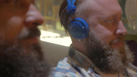 Close up view of two bearded men listening musics using colorful on-ear headset Image