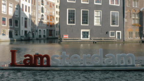 View of small plastic figure of Iamsterdam letters sculpture on the bridge again Footage