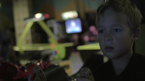 Close up view of small boy are playing video arcade game in game center Footage