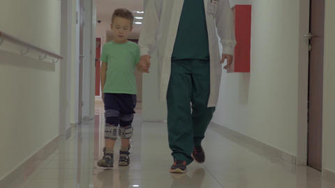 Doctor and child walking in hospital corridor Footage