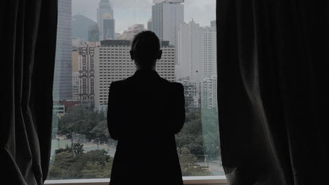 Slow motion clip of woman opening curtains on the view of Hong Kong, China Footage