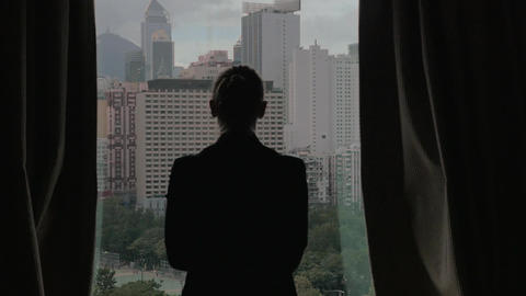Woman opening curtains and looking at Hong Kong Footage