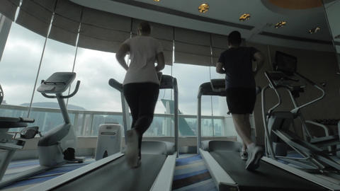 In Hong Kong, China in gym on treadmills running young woman and man Footage