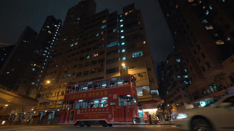 Seen night city and skyscrapers with a busy road with passing double-decker buse Footage