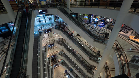 Timelapse of people on escalators in multistorey shopping mall Footage