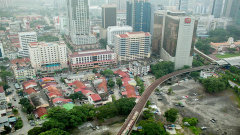 Bird eye time lapse view of railways across road against city landscape. Kuala L Footage