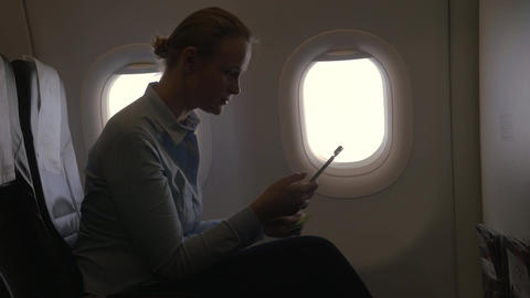 In airplane view of woman making payment with bank card using smartphone and don Footage