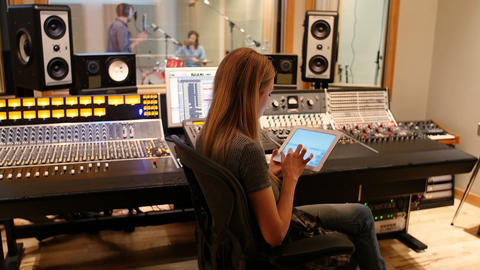 Female audio engineer using sound mixer using digital tablet Footage