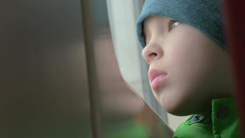 Close up view of small boy bored face in winter hat on his place in the rail tra Footage