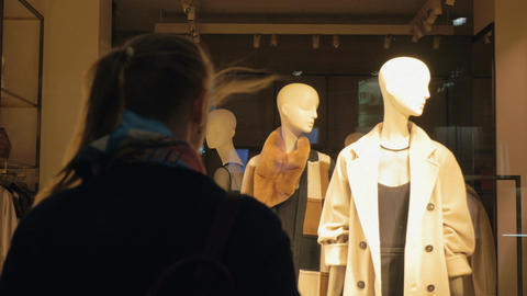 Back view of woman going to the shop window with female mannequins Live Action