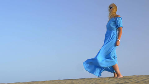 Slow motion view of young blond woman standing against blue sky in long blue dre Live Action