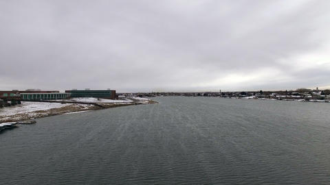 Aerial drone lift up over high school windy lake to dark overcast grey skies Footage