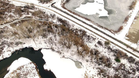 Aerial drone tilt down winter downtown city drop to snowy creekside ground Footage