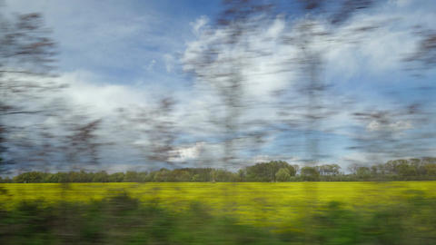 View from riding train window of coutryside landscape against cloudy sky Footage