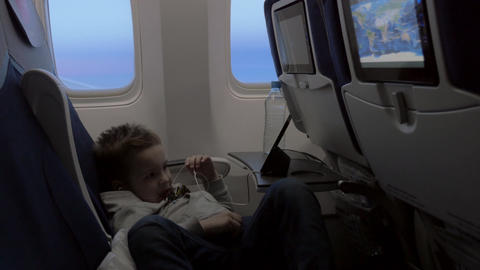 Child watching cartoon on smartphone in airplane Footage