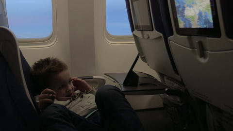 View of little boy watching films in headset in the aircraft lying on the seat a Footage