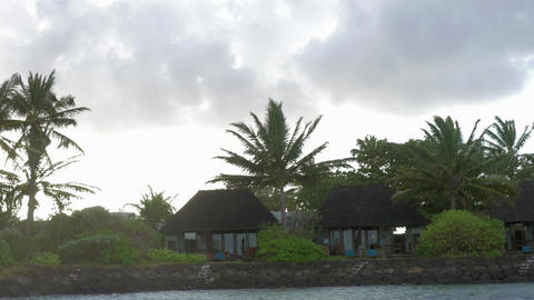 View of moving along coast with luxury bungalow hotel against cloudy sky, Maurit Footage