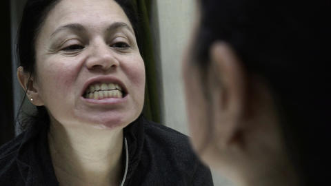 Woman Looking into Mirror Inspecting Her Teeth Handheld Live Action
