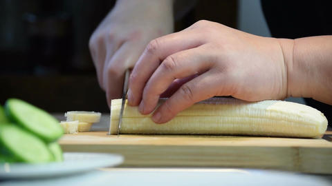 Close-up of professional chef's hand using knife to slice a banana for cooking A Footage