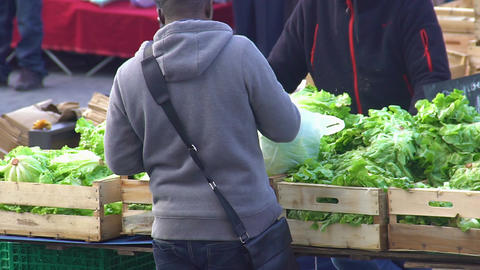 Young male buying fresh greens at the local market, organic food, eco products Footage