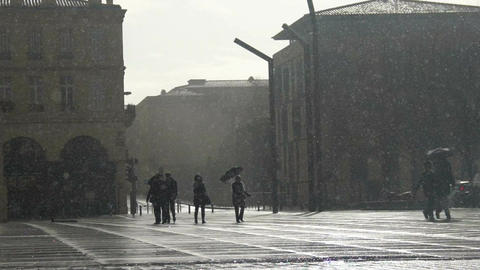 People walking with umbrellas under freezing rain, sleet, bad weather conditions Footage