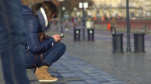 Sad woman sitting on sidewalk with smartphone, checking message with bad news Live Action