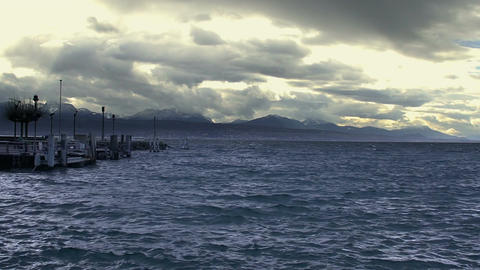 Waves splashing on choppy water surface, stormy cloudscape, mountains on horizon Footage