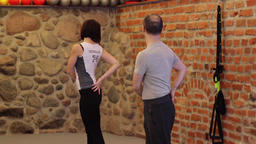 Man is working out with personal trainer at fitness center Archivo