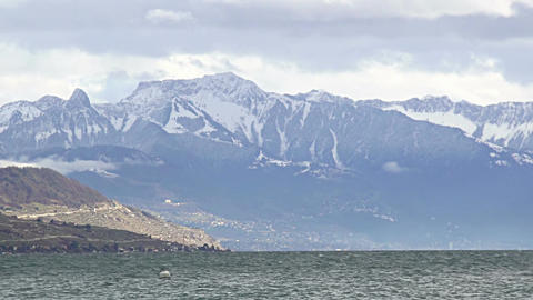Water rippling in Lake Geneva, majestic Alps mountain ridge with snowy peaks Footage