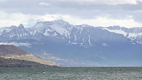 Water rippling in Lake Geneva, majestic Alps mountain ridge with snowy peaks Footage