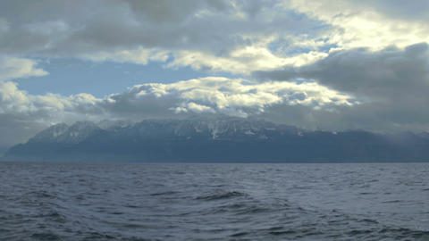 Stormy weather in Swiss Alps, thick clouds covering sky, lake waves splashing Footage