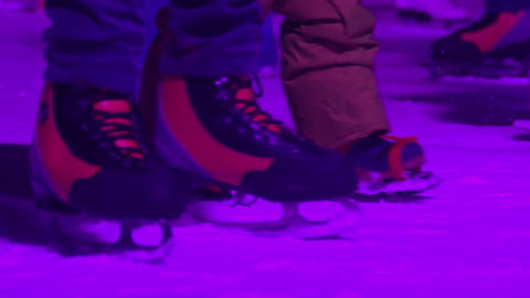 Feet of parent helping child to skate on illuminated ice rink, family leisure Footage
