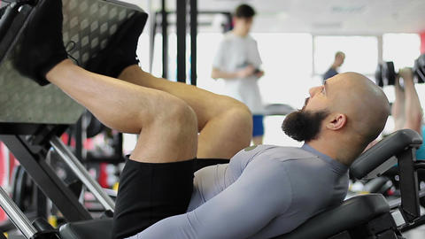 Muscular male athlete doing leg press exercise, working out at fitness club Footage
