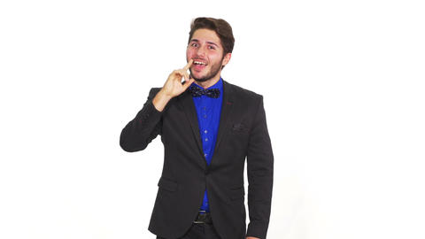 Happy young unconvinced man on a white background pointing with a finger Footage