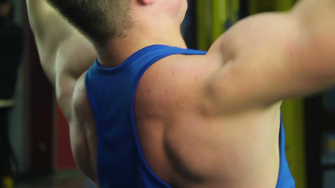 Strained shoulders of muscular man doing pulldown exercise, active workout Live Action
