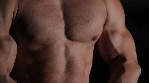 Strong bodybuilder's muscular torso, sportive man showing perfect body, closeup Live Action