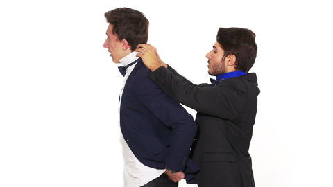 Fashion dressed up guys putting each other their bows Footage