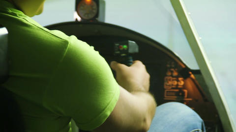 Male teenager sitting in airplane cockpit simulator and showing OK hand sign Footage