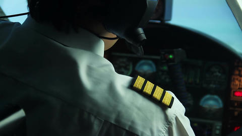 Male pilot checking control panel and reporting situation to flight dispatcher Live Action