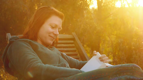 Young, beautiful, smiling woman relaxs on a deck-chair reading a book in sunset Filmmaterial