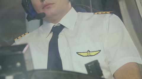 Pilot's insignia on uniform, captain controlling airliner, thinking about home Live Action