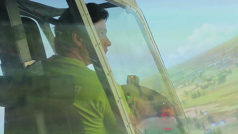 Young man looking at green landscape through flight simulator window, aviation Footage