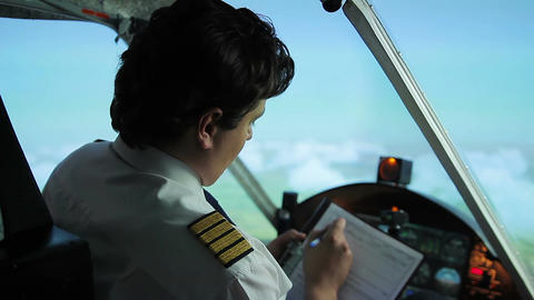Airplane captain switching to autopilot mode, writing flight details in document Footage