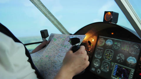 Male pilot holding steering wheel, checking route to flight destination on map Footage