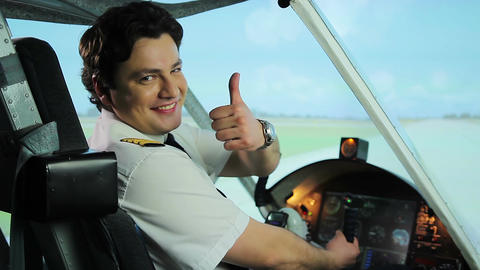 Successful pilot smiling for camera with thumbs up gesture, satisfied with job Footage
