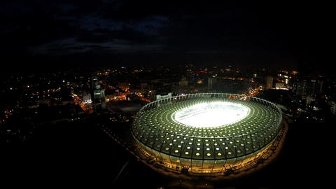 Illuminated modern stadium, lights sparkling in night megalopolis, aerial view Footage