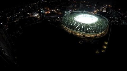 Soccer match begins at illuminated stadium, aerial shot, camera moving closer Footage