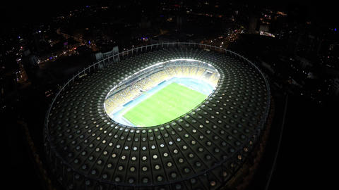 View from above on amazing illuminated football stadium at night time, city Footage