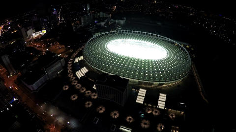 Oval-shaped illuminated football stadium, aerial view on beautiful night city Footage