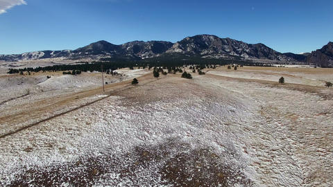 Aerial drone fly winter snowy dusted fields to mountain backdrop ビデオ